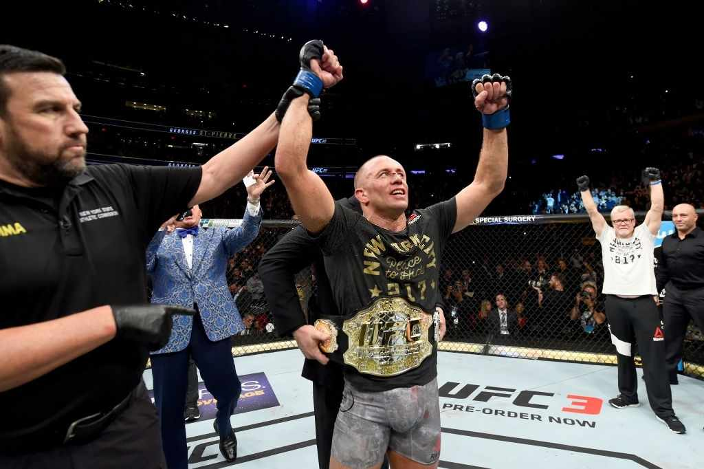 St-Pierre of Canada celebrates his victory over Michael Bisping of England in their UFC middleweight championship bout during the UFC 217