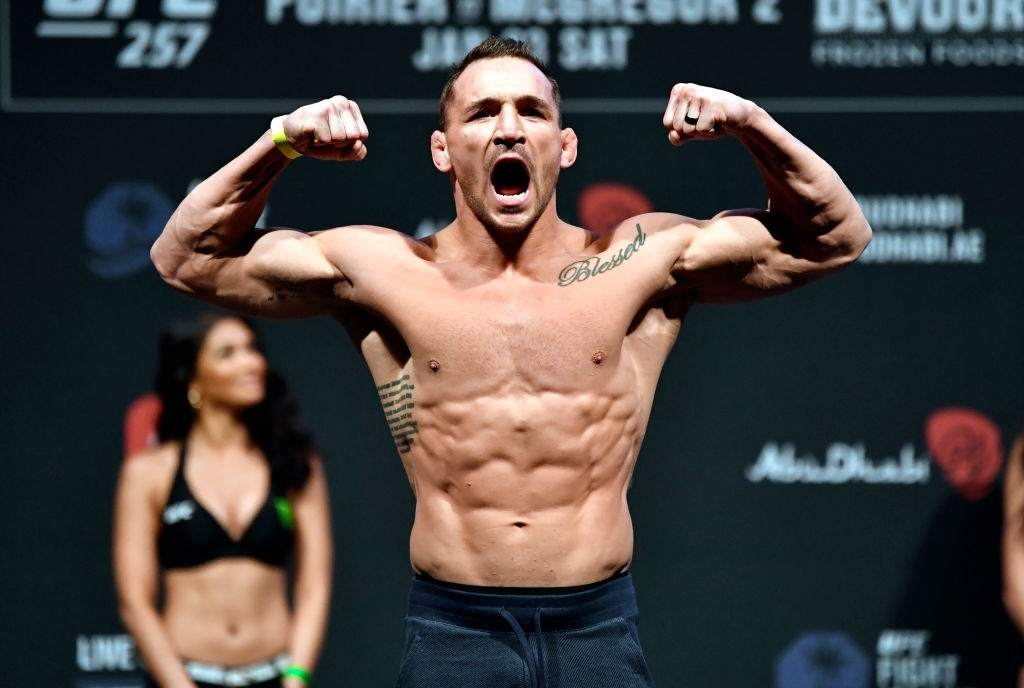 Michael Chandler poses on the scale during the UFC 257 weigh-in at Etihad Arena on UFC Fight Island
