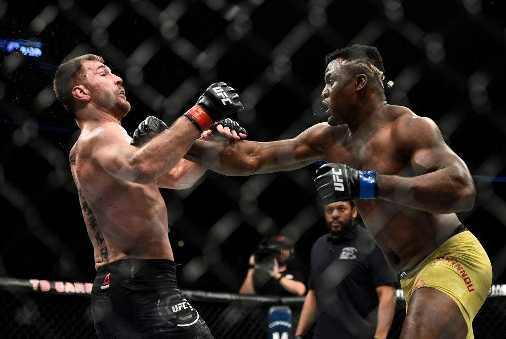 Francis Ngannou of Cameroon punches Stipe Miocic in their heavyweight championship bout during the UFC 220
