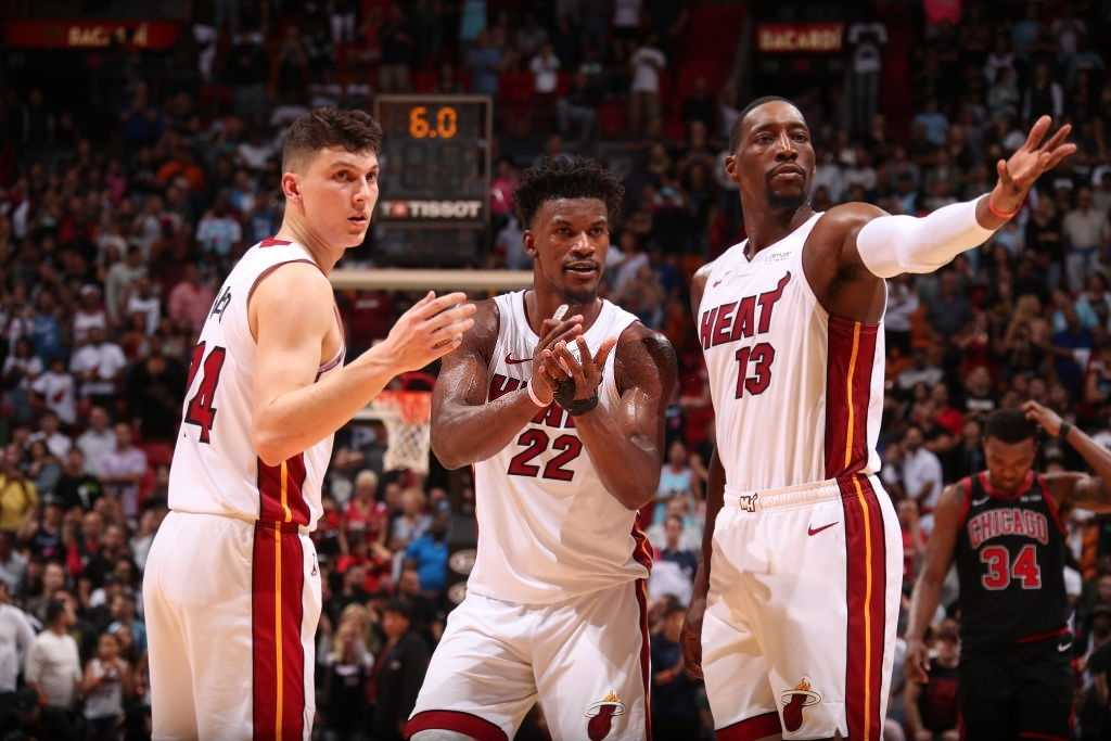 Tyler Herro #14 of the Miami Heat, Jimmy Butler #22 of the Miami Heat, and Bam Adebayo #13 of the Miami Heat look on during a game