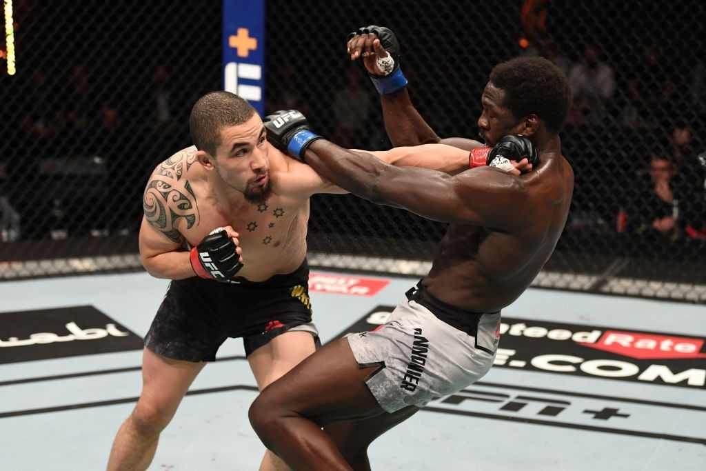 Robert Whittaker of Australia punches Jared Cannonier in their middleweight bout during the UFC 254 event on October 25, 2020 on UFC Fight Island, Abu Dhabi, United Arab Emirates.
