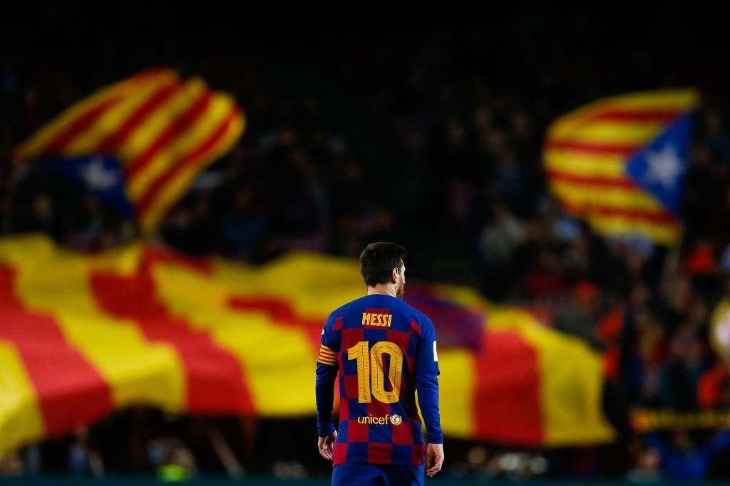 Lionel Messi of FC Barcelona walks for the pitch with a catalan independence flag in the background (Photo by Eric Alonso/MB Media/Getty Images)