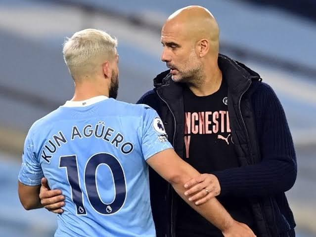 Manchester City manager Pep Guardiola and Player Sergio Aguero talking during a match.