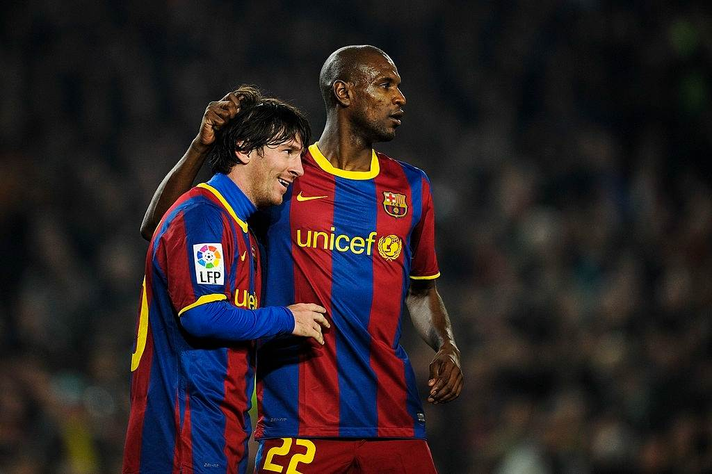 Lionel Messi and Eric Abidal sharing a moment in Barcelona colours.