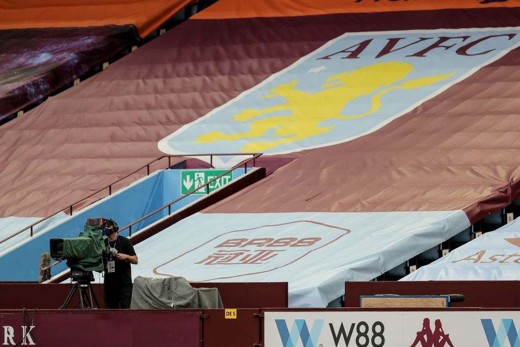 BIRMINGHAM, ENGLAND - JUNE 17: A TV Camera man for Sky Sports is seen social distancing in a stand with a load of flags and banners prior to the Premier League match between Aston Villa and Sheffield United at Villa Park on June 17, 2020 in Birmingham, United Kingdom. (Photo by Matthew Ashton - AMA/Getty Images)