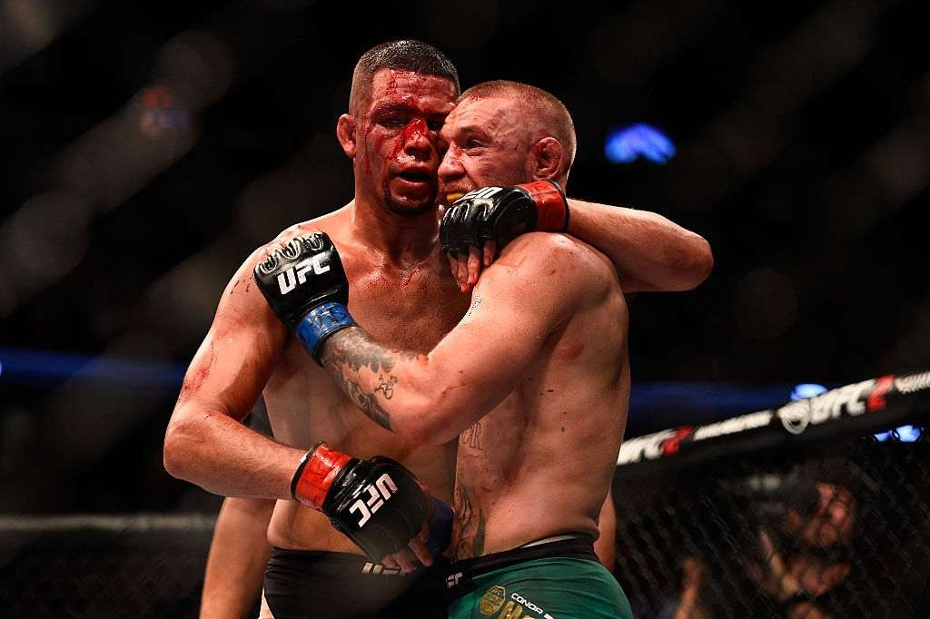 Nate Diaz and Conor McGregor of Ireland embrace after finishing five rounds in their welterweight bout during the UFC 202 event