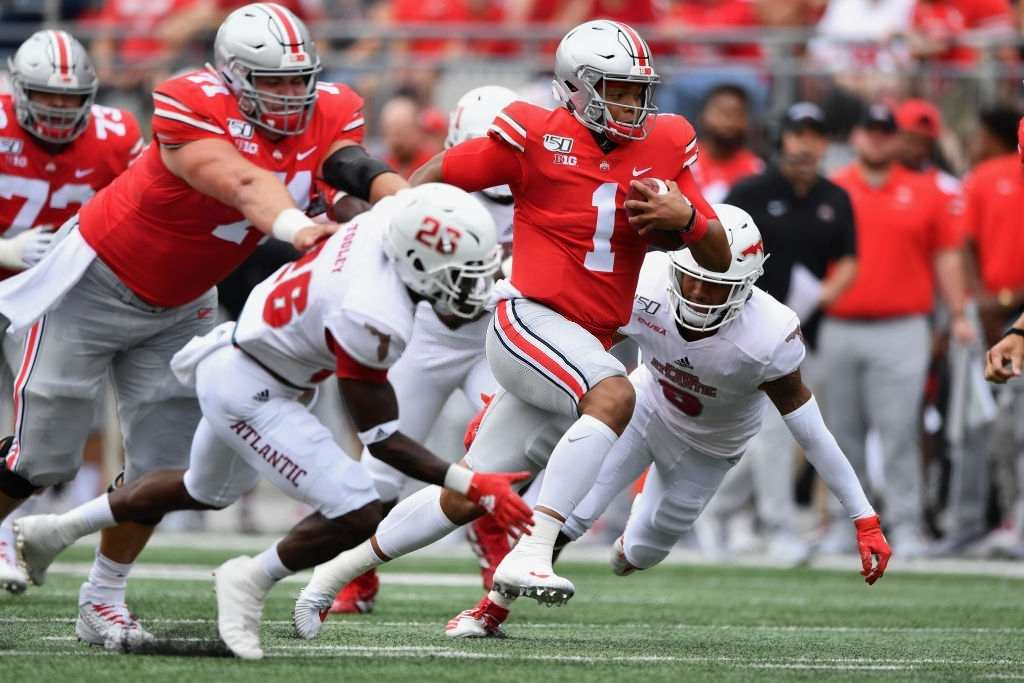Quarterback Justin Fields #1 of the Ohio State Buckeyes breaks free for a 51-yard touchdown run in the first quarter