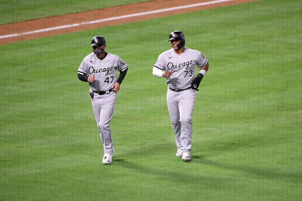 Yermin Mercedes #73 of the Chicago White Sox celebrates his RBI double with third base coach Joe McEwing #47