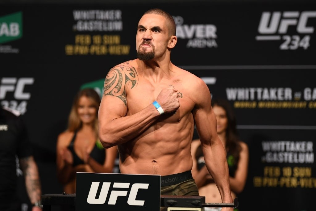Robert Whittaker showcases his strength at the weigh-ins.