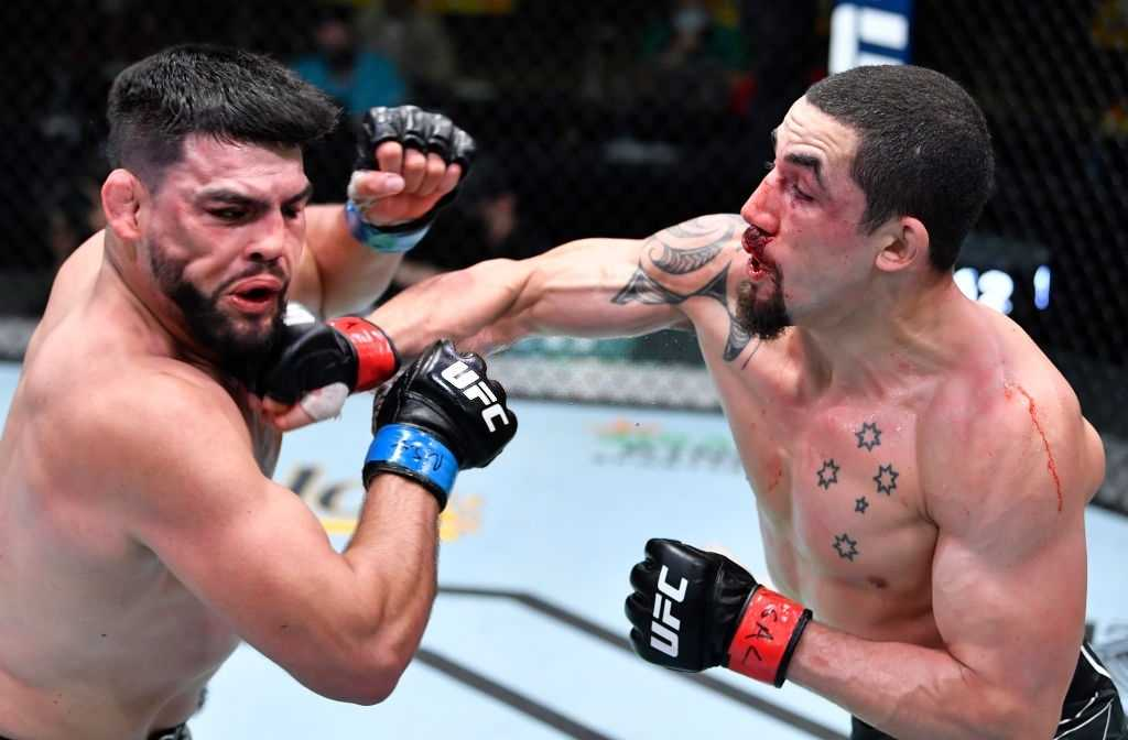 Robert Whittaker of Australia punches Kelvin Gastelum in a middleweight fight during the UFC Fight Night event at UFC APEX on April 17, 2021 in Las Vegas, Nevada.