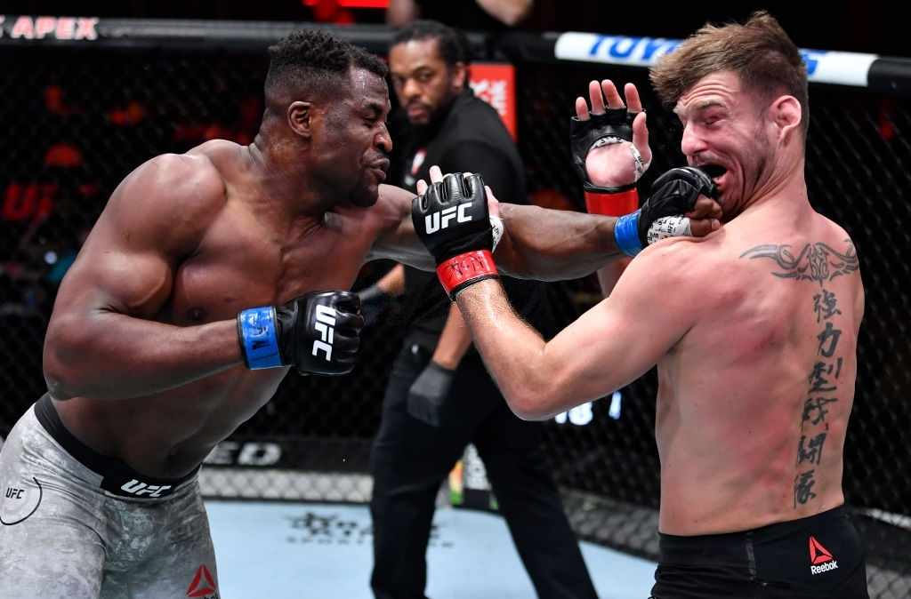 Francis Ngannou of Cameroon punches Stipe Miocic in their UFC heavyweight championship fight during the UFC 260 event at UFC APEX on March 27, 2021 in Las Vegas, Nevada.