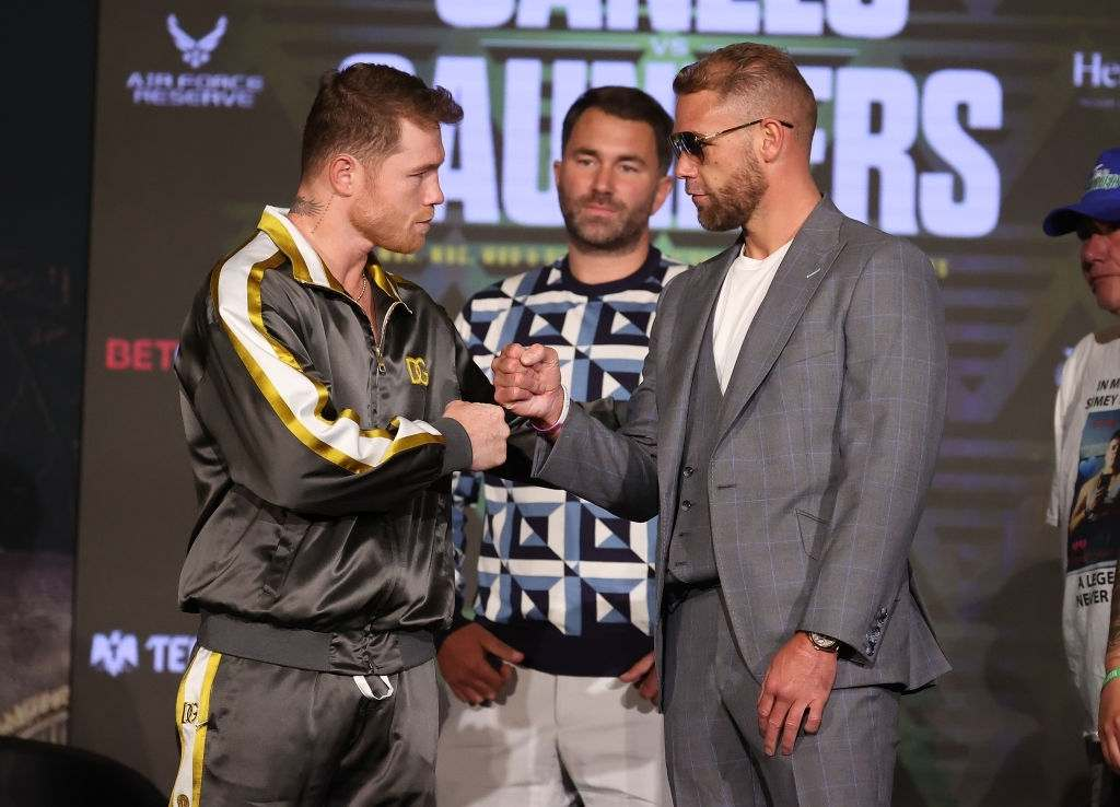Canelo Alvarez and Billy Joe Saunders shake hands with Matchroom Promoter Eddie Hearn looking on during the press conference.