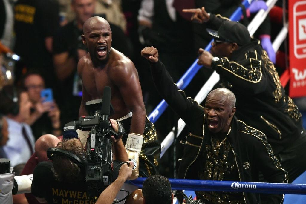 Floyd Mayweather Jr. (L) and Floyd Mayweather Sr. celebrate after defeating Conor McGregor.
