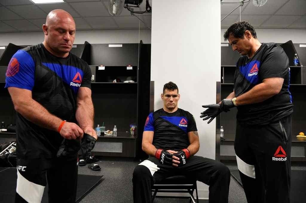 Matt Serra, Chris Weidman and Ray Longo wait backstage during the UFC Fight Night event inside the Nassau Veterans Memorial Coliseum on July 22, 2017 in Uniondale, New York.