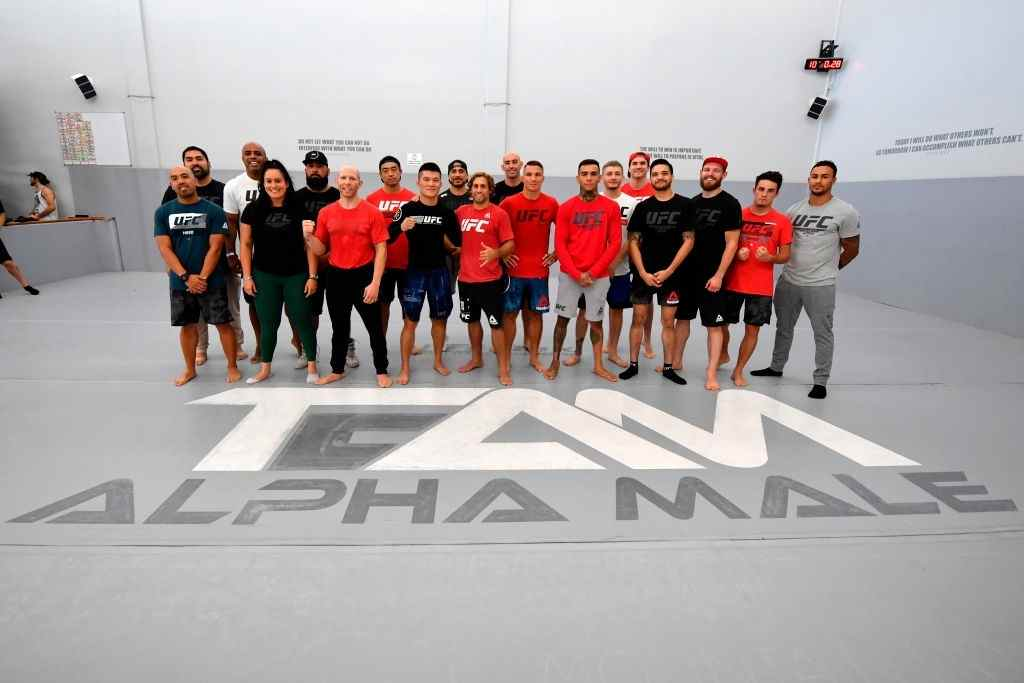 Team Alpha Male fighters Pingyuan Liu of China, Urijah Faber, Darren Elkins, Josh Emmett, Andre Fili and Benito Lopez pose with their teammates for a group photo during the open workouts at Urijah Faber's Ultimate Fitness on July 10, 2019 in Sacramento, California.