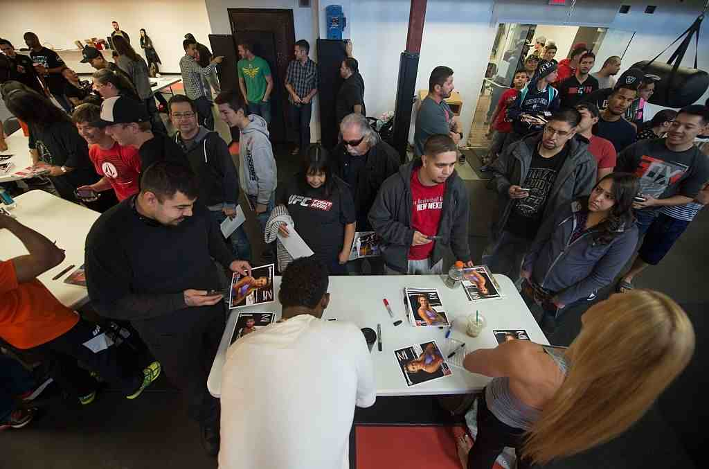 Holly Holm and Jon Jones sign autographs for fans during the Jackson Wink MMA Academy Grand Opening at Jackson's Mixed Martial Arts & Fitness on October 31, 2015 in Albuquerque, New Mexico.