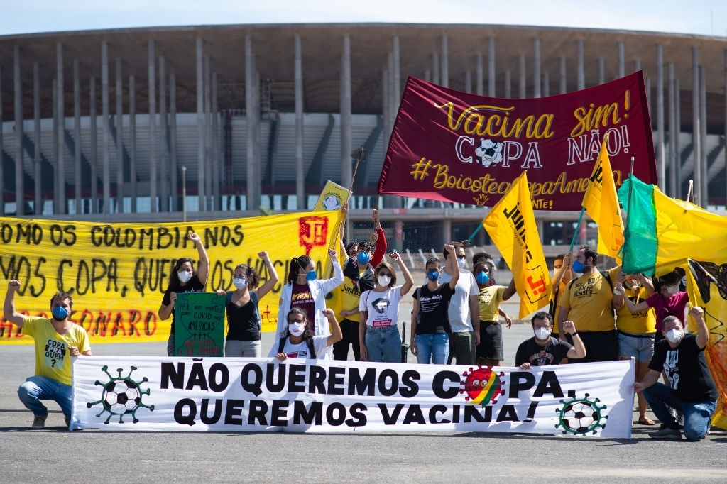 Protesters hold banners stating they don't want the Copa America 2021