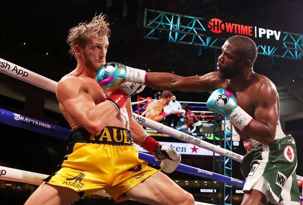 Floyd Mayweather (R) punches Logan Paul during their contracted exhibition boxing match at Hard Rock Stadium on June 06, 2021 in Miami Gardens, Florida.